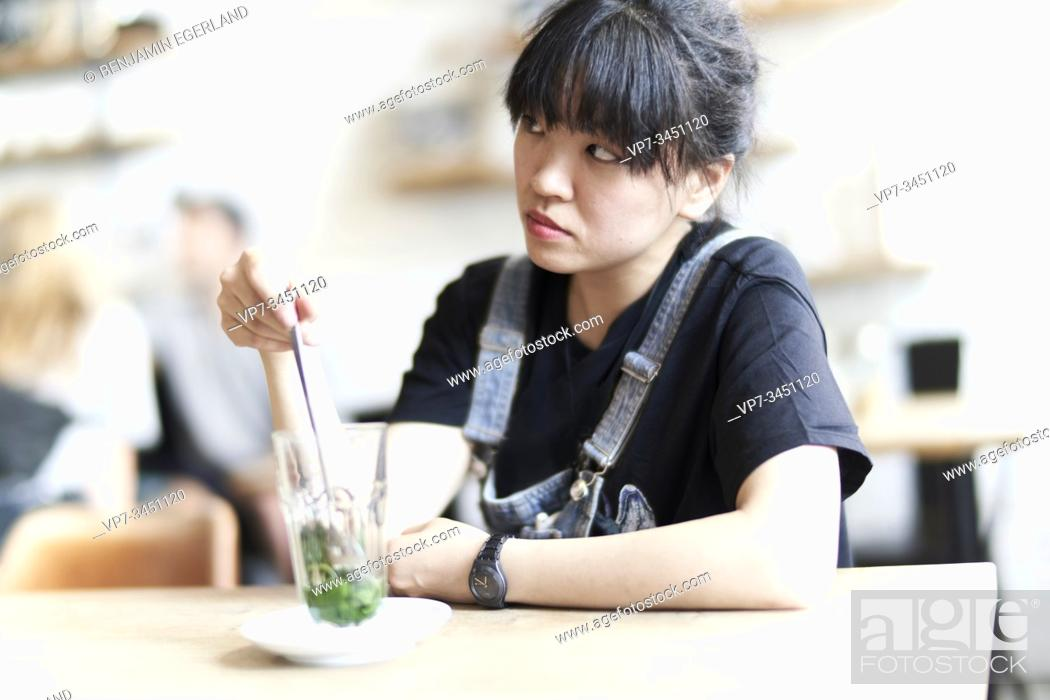 Stock Photo: Korean woman sitting at table in cafe with drink.