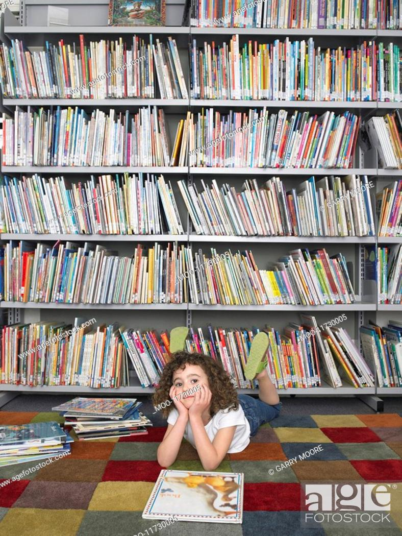 Stock Photo: Girl lying on stomach in front of library bookshelf.