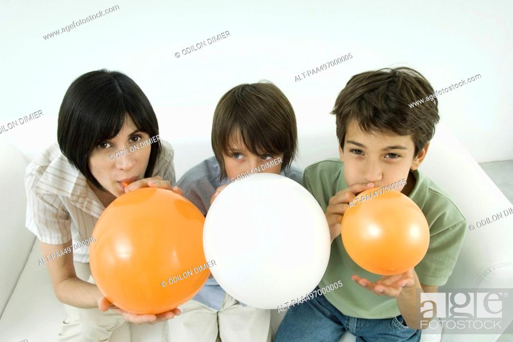 Stock Photo: Mother and two sons inflating balloons, woman and one son looking at camera.