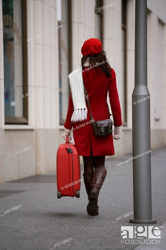 Stock Photo: A woman walking along the street with a suitcase.