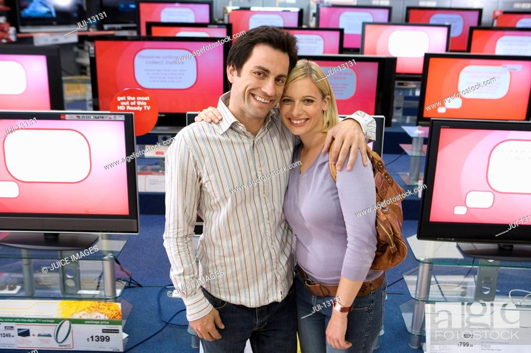 Stock Photo: Young couple arm in arm in electronics shop, smiling, portrait, elevated view.