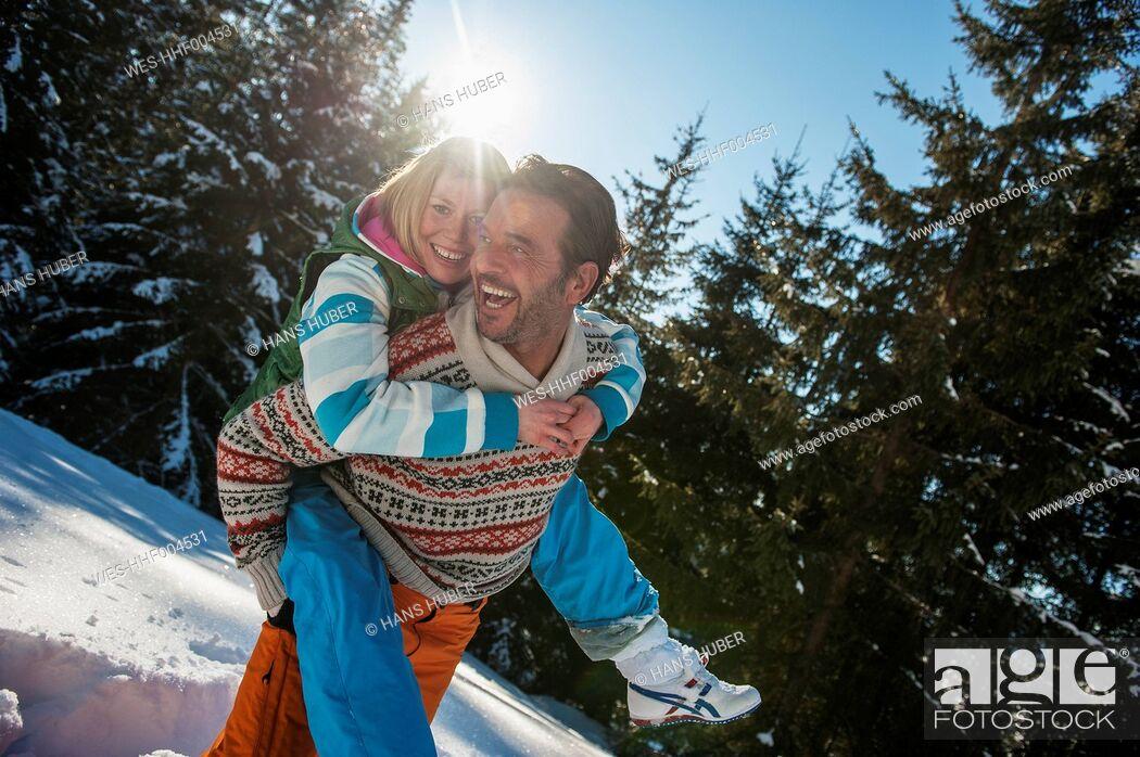 Stock Photo: Austria, Salzburg, Man giving piggyback ride to woman, smiling.