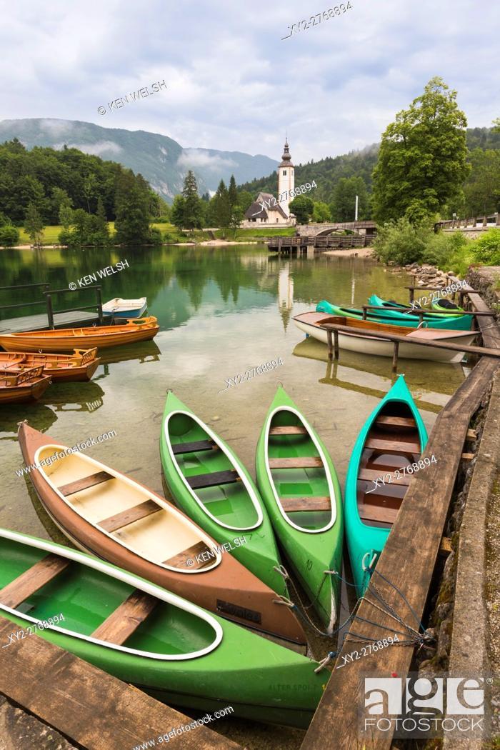 Stock Photo: Lake Bohinj (Bohinjsko jezero), Triglav National Park, Upper Carniola, Slovenia. Canoes for rent. The church of St. John (Cerkev sv Janeza) at Ribcev Laz in.
