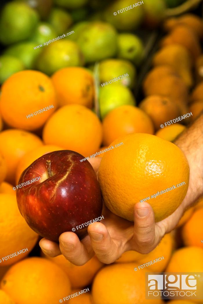 Stock Photo: Close-up of Caucasian male hand holding apple and orange.