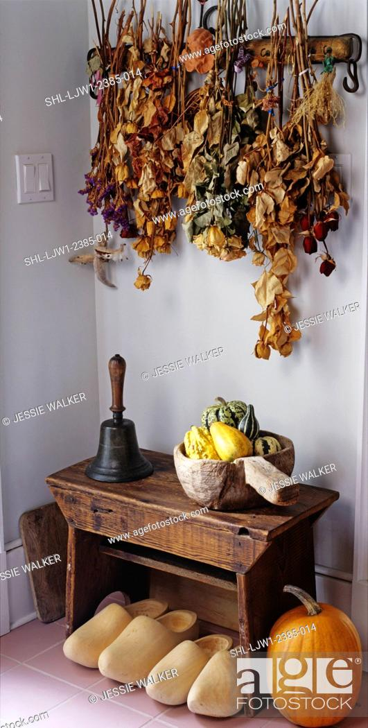 Stock Photo: entry ways: area decorated with dried flowers hanging from wall, small bench with old hand bell, wooden bowl filled with gourds, dutch shoes.