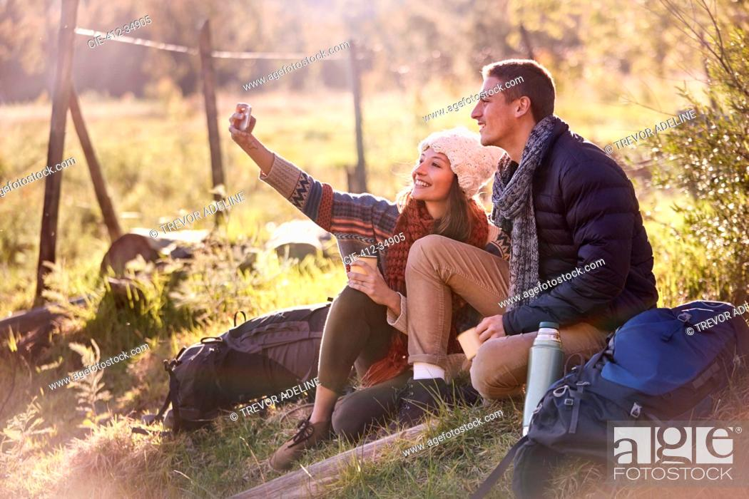 Photo de stock: Young couple taking a break from hiking, taking selfie with camera phone.