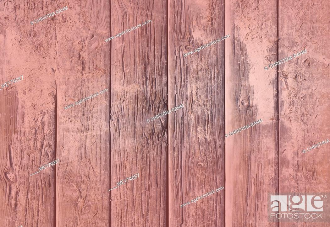 Stock Photo: Weathered wood background texture. Old rugged planks with screws for background texture toned in Living Coral color.