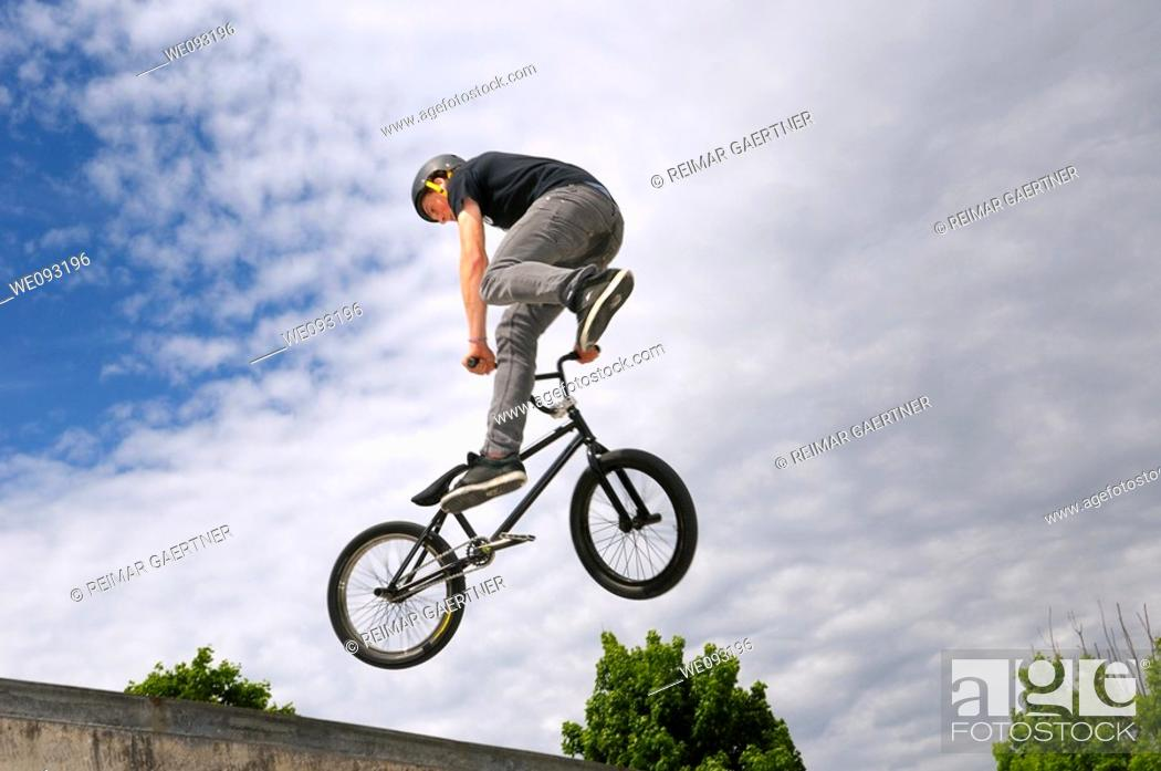 Stock Photo: BMX bike rider exiting a bowl air out with a Tail Whip 360 spin.