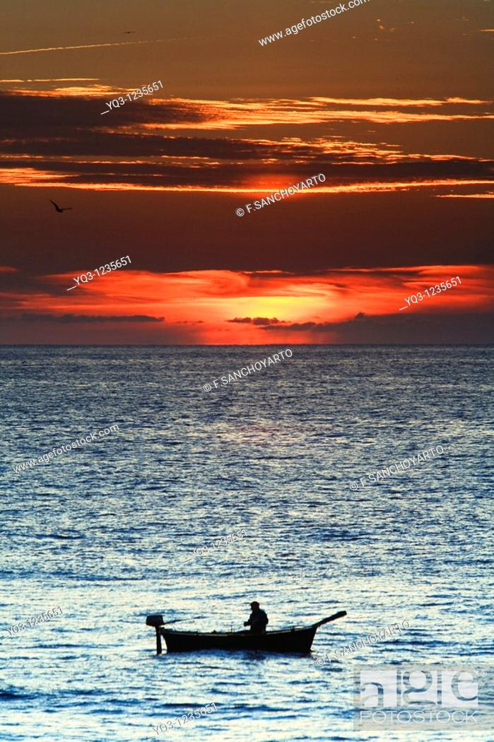 Stock Photo: Fisherman in his boat at sunrise. Castro Urdiales, Cantabria, Spain.