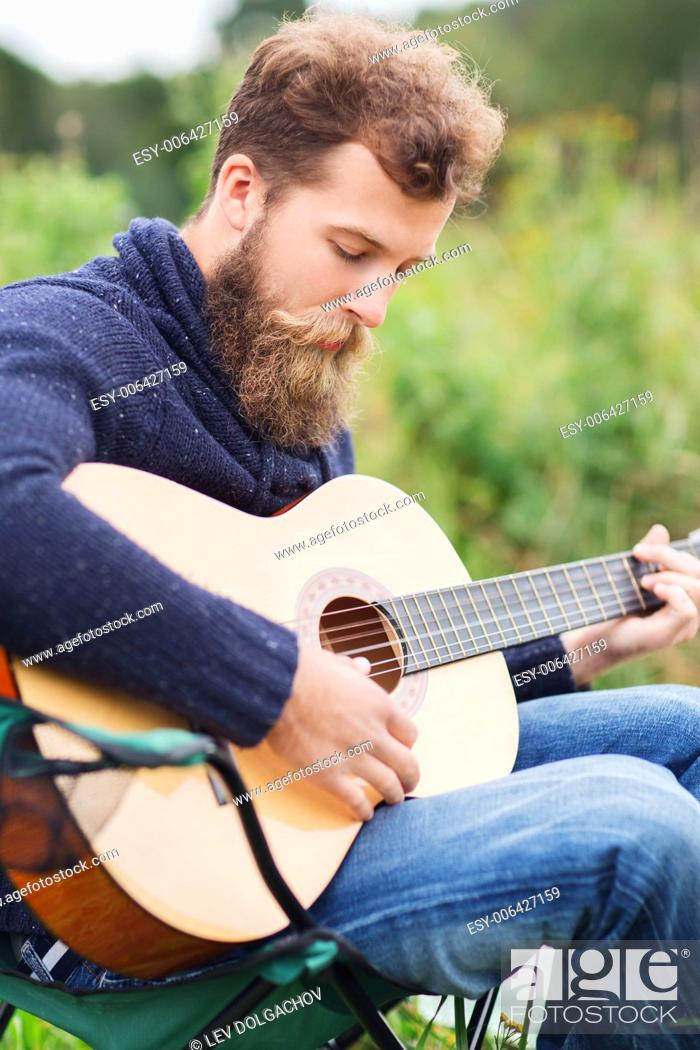Imagen: adventure, travel, tourism, music and people concept - man with beard playing guitar in camping.