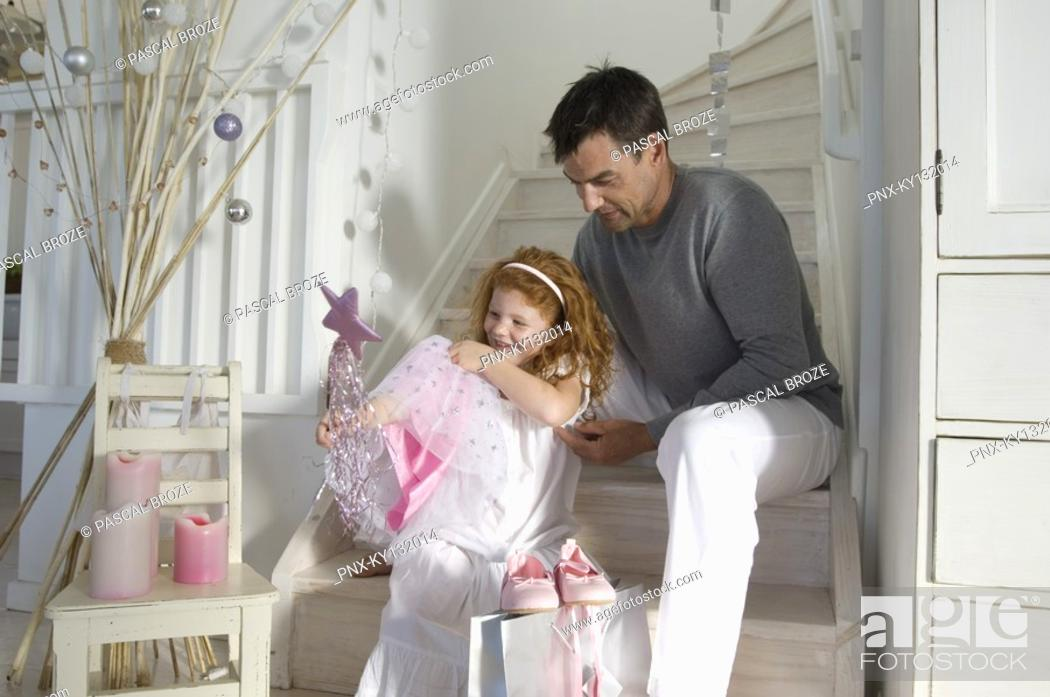 Stock Photo: Father and daughter opening Christmas presents, girl holding a princess costume, indoors.