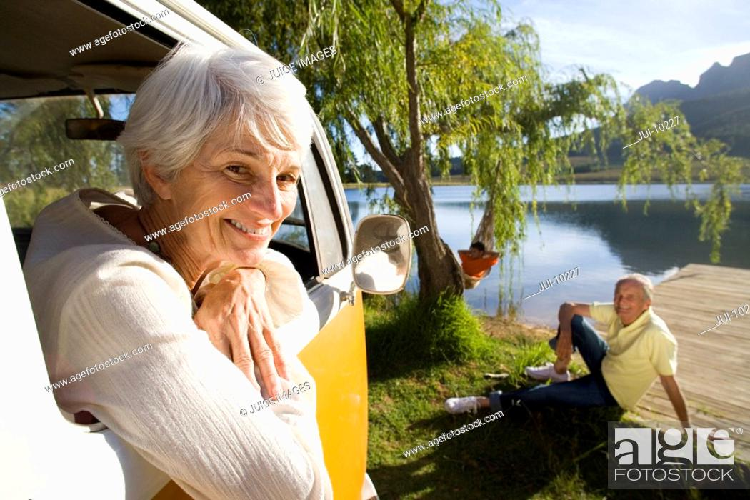 Stock Photo: Portrait of senior woman leaning from window of camper van by lake, senior man on jetty in background.