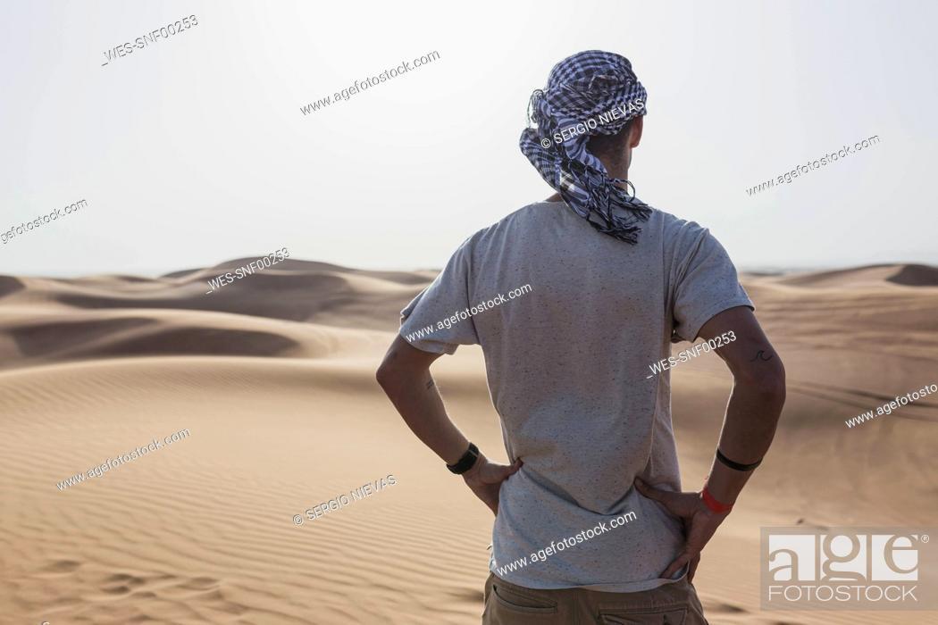 Stock Photo: Male tourist standing on sand dunes in desert at Dubai, United Arab Emirates.