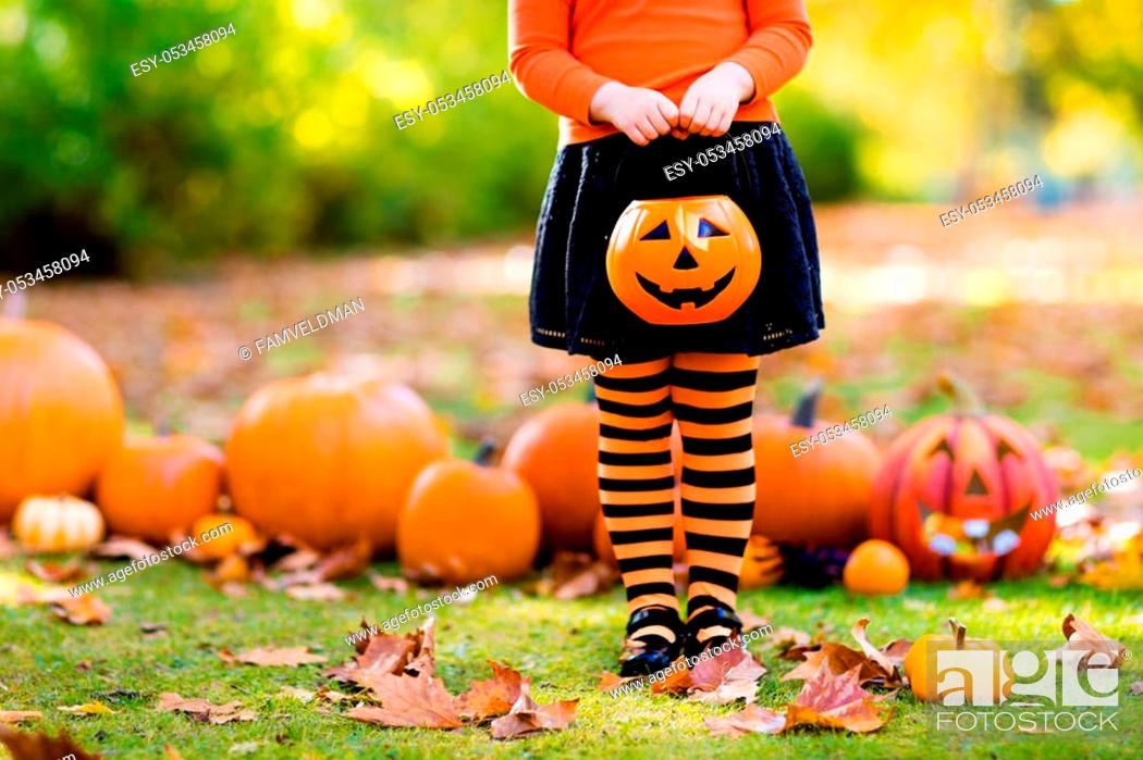 Stock Photo: Kids with pumpkin on Halloween. Little girl in witch costume and hat playing in autumn park. Child at Halloween trick or treat. Kid trick or treating.