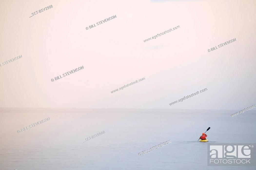 Stock Photo: A man kayaking on Lake Tahoe in the fog in winter.
