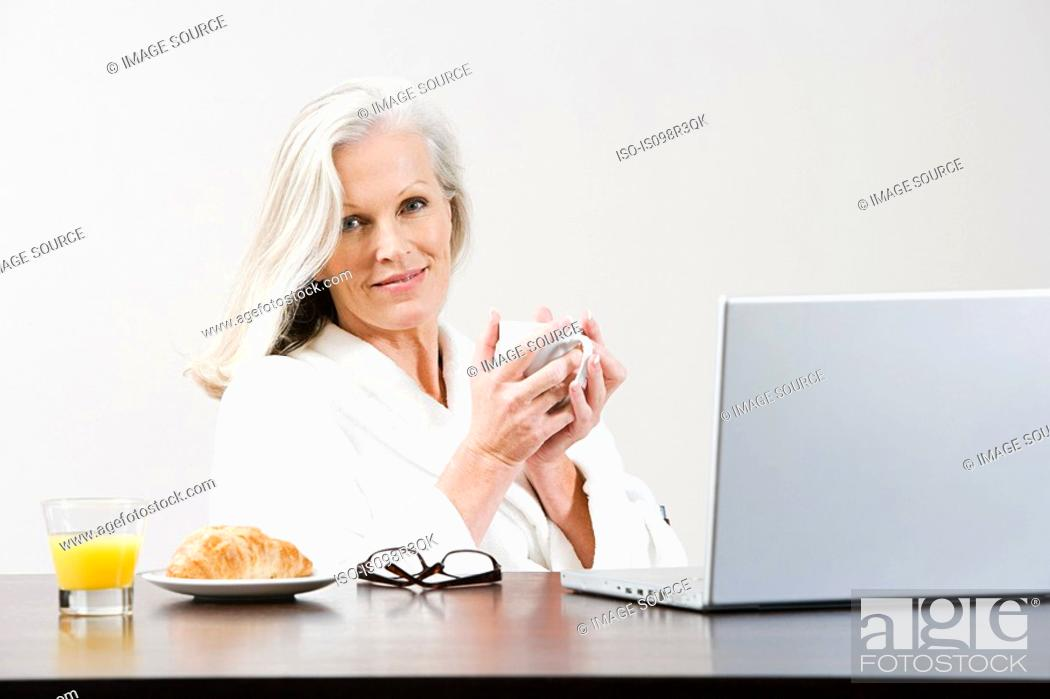 Stock Photo: Middle aged woman eating breakfast while using laptop.