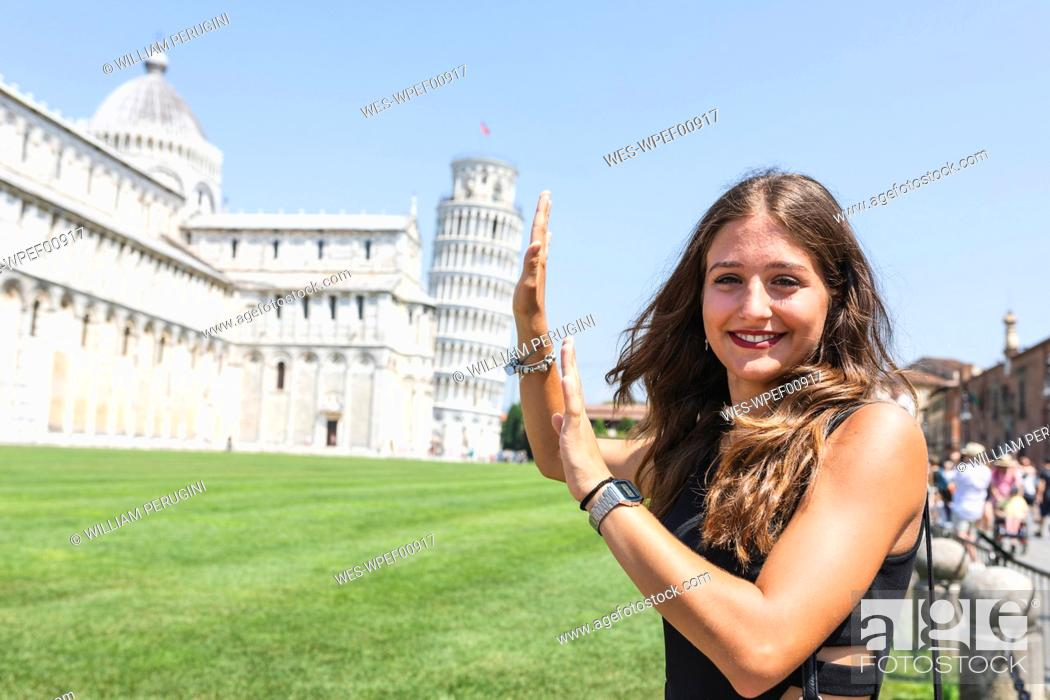 Stock Photo: Italy, Pisa, portrait of young woman posing with the Leaning Tower in background.