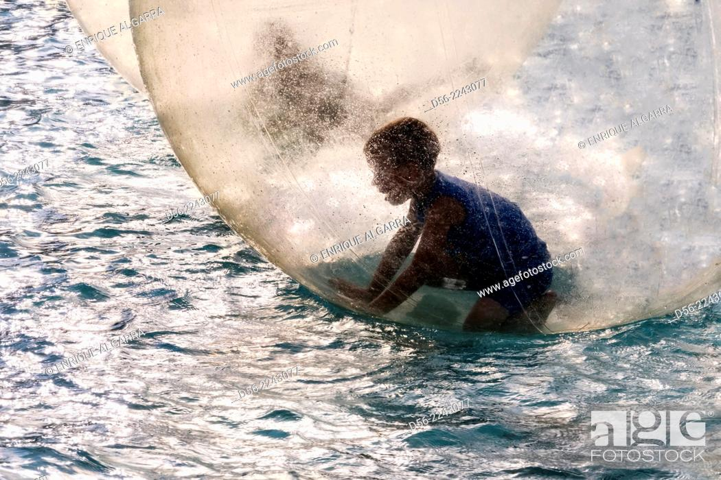 Stock Photo: boy inside a bubble floating on a pool, City of Arts and Sciences, Valencia, Spain.