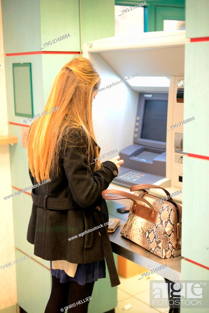 Stock Photo: Young Woman or Student Withdrawing Money from Cash Machine in Bank Aix-en-Provence France.