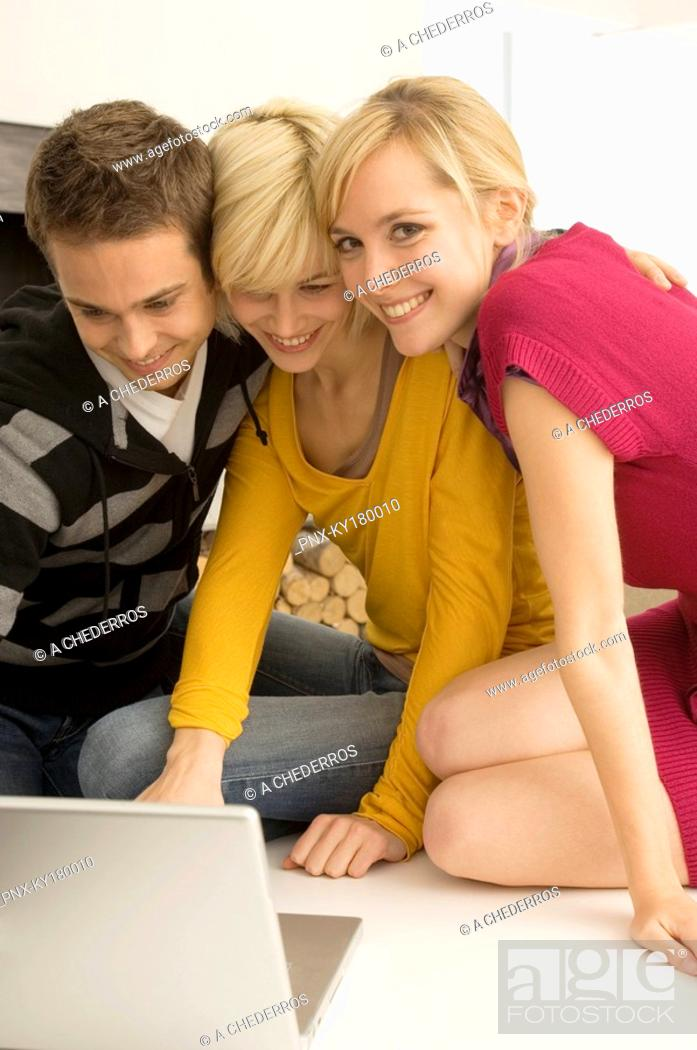 Stock Photo: Two young women and a young man using a laptop and smiling.