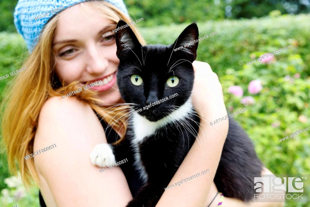Stock Photo: Portrait of a smiling young woman holding cat on her arms.