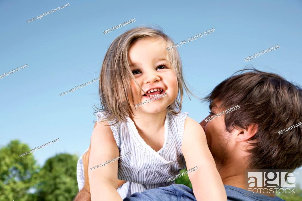 Stock Photo: Germany, Cologne, Father holding her daughter, smiling.