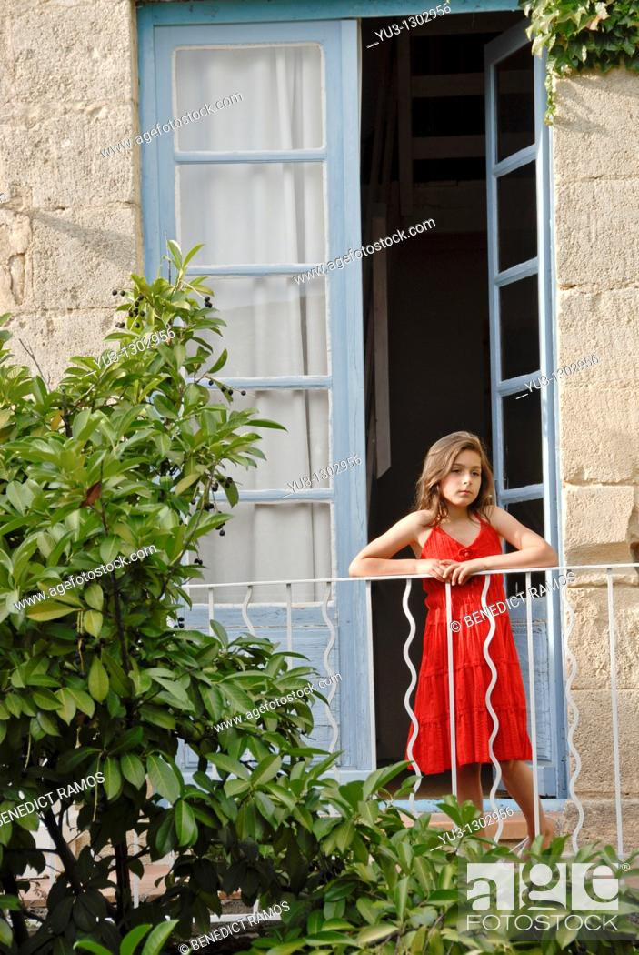 Stock Photo: Young girl in red dress on balcony of French house.