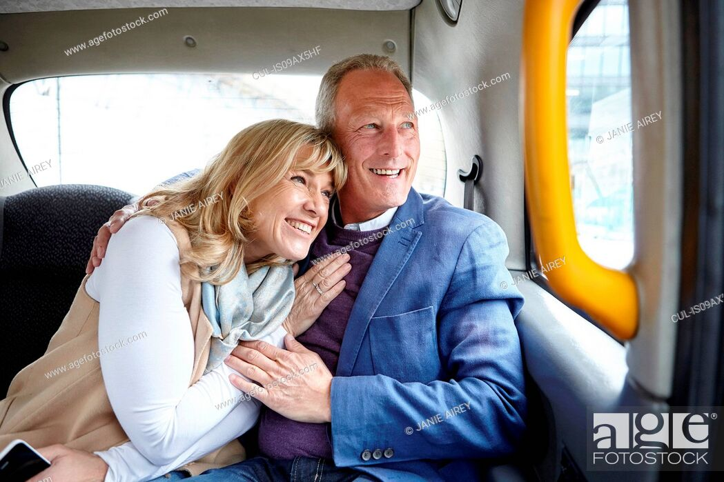 Stock Photo: Mature romantic dating couple en route in black cab backseat.