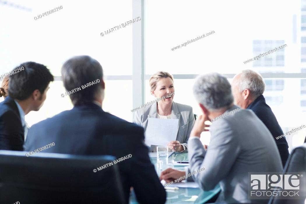 Stock Photo: Smiling businesswoman leading meeting in conference room.
