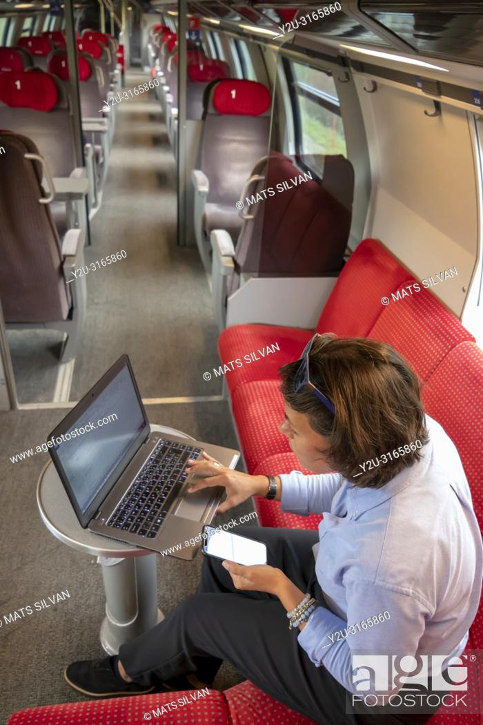 Stock Photo: Business Woman Working on Laptop and Smartphone in First Class in a Train in Switzerland.