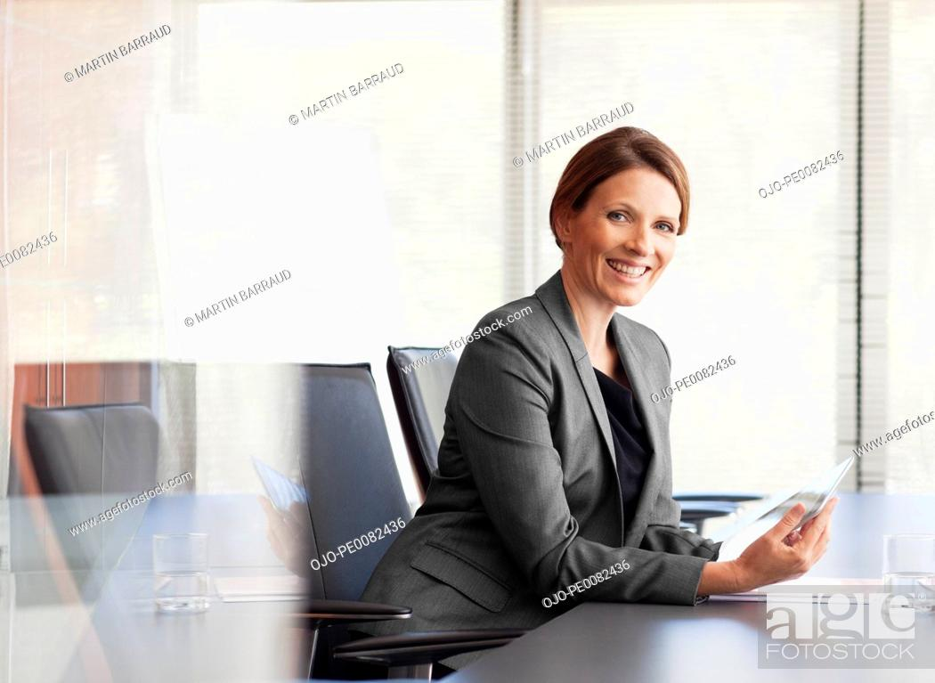 Stock Photo: Portrait of smiling businesswoman with digital tablet in conference room.