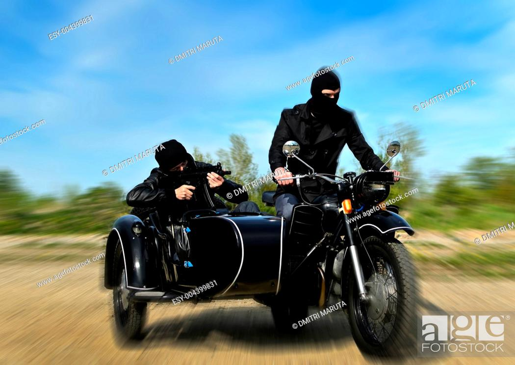 Stock Photo: Two armed men riding a motorcycle with a sidecar. Motion blur.
