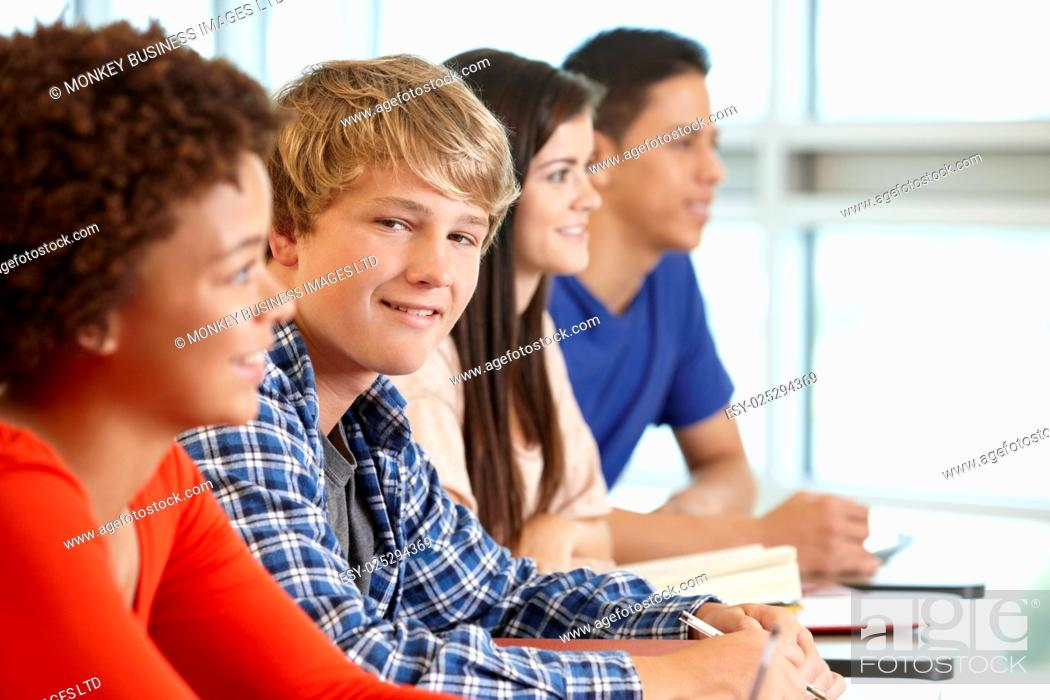 Stock Photo: Multi racial teenage pupils in class, one smiling to camera.