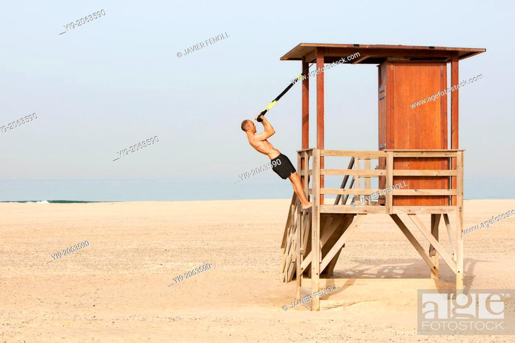 Imagen: man playing sports on the beach with trx.