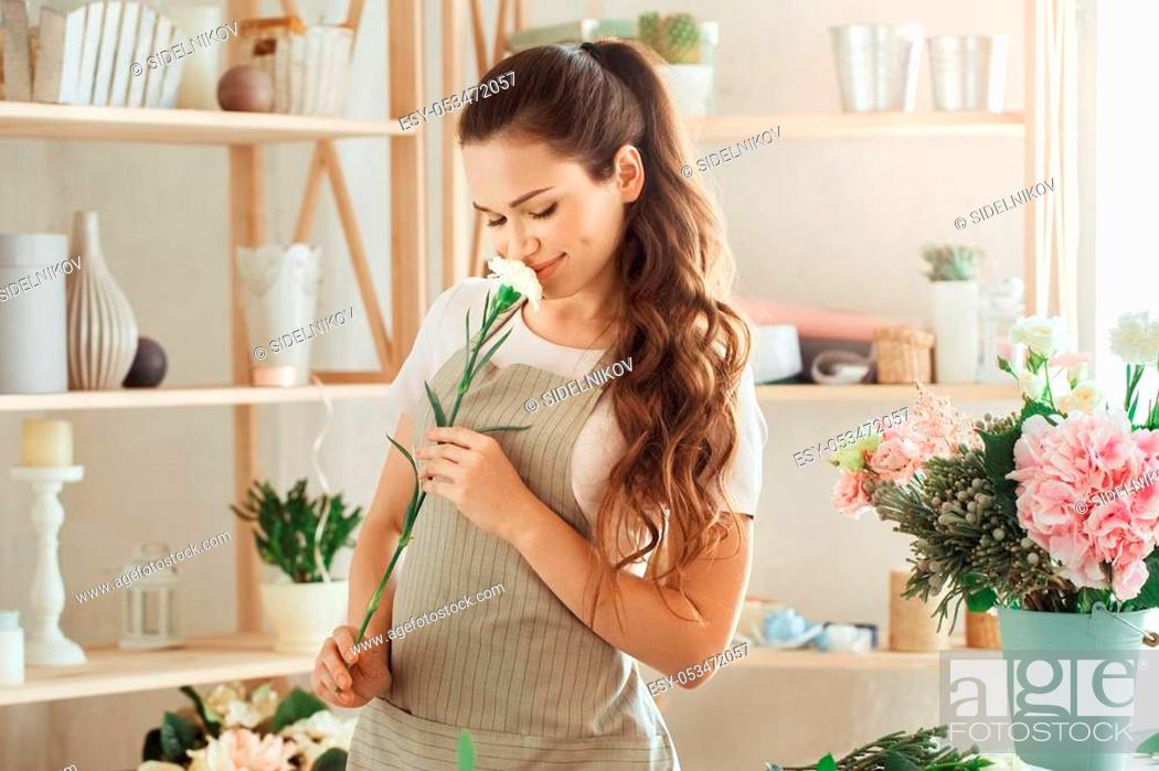 Stock Photo: Young female florist working with flowers smell.
