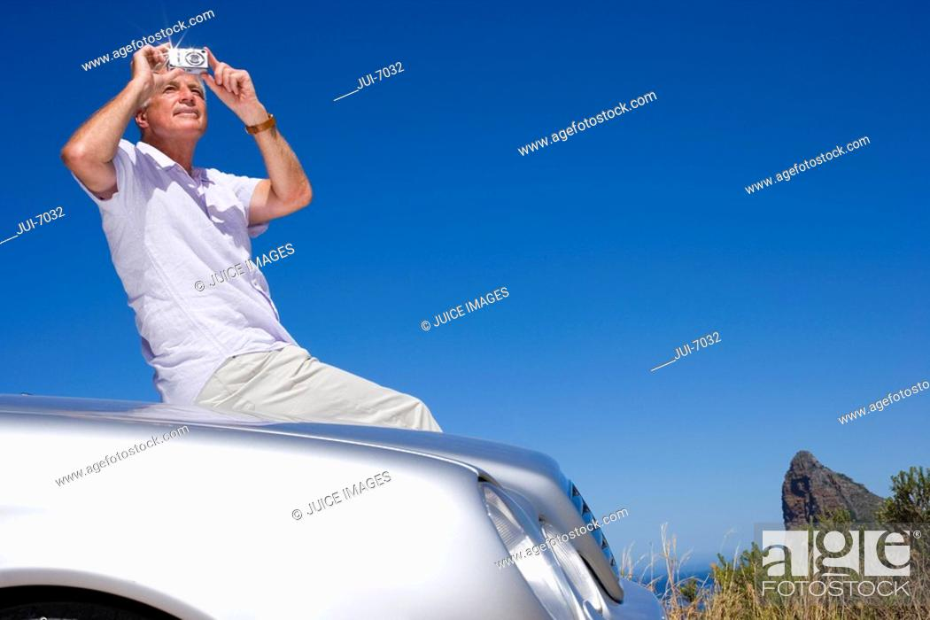 Stock Photo: South Africa, Western Cape, senior man sitting on car bonnet on clifftop overlooking Atlantic Ocean, using camera, smiling, portrait.