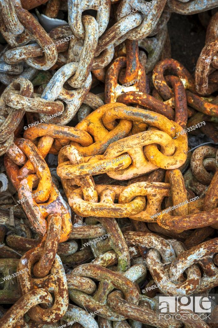 Stock Photo: Old rusty industrial heavy duty chains lying at a workplace, Ayrshire, Scotland, UK.