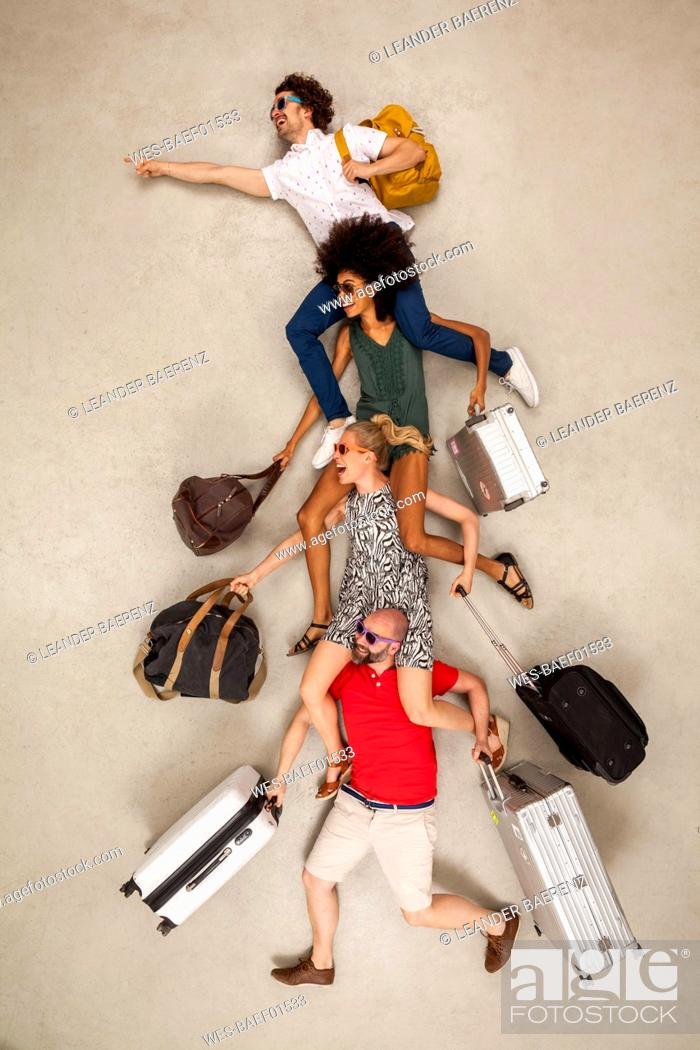 Stock Photo: Tour group sitting on each other's shoulders, carrying luggage.
