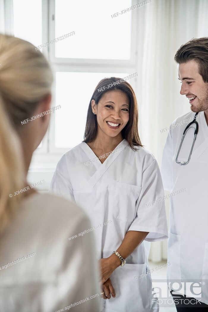 Stock Photo: Doctors standing and talking with woman.