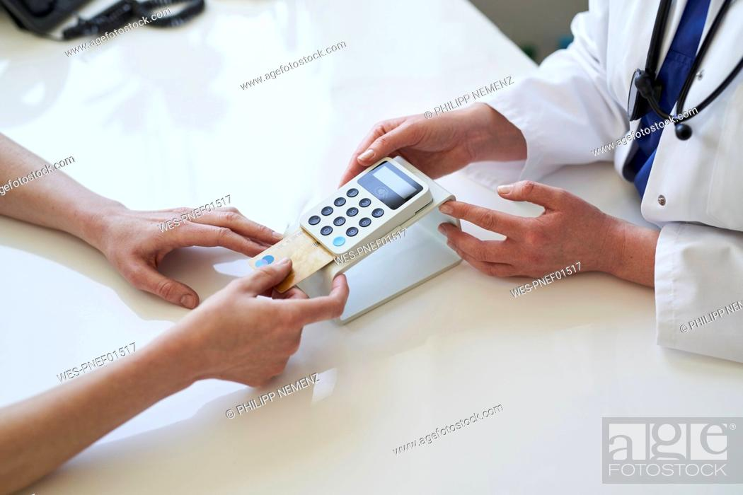 Stock Photo: Doctor and patient with card and card reader at medical practice.