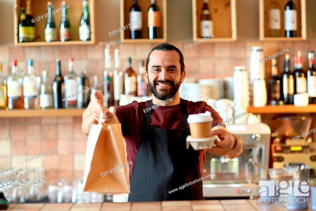 Stock Photo: small business, people, takeaway and service concept - happy man or waiter in apron holding coffee cups and paper bag at bar.