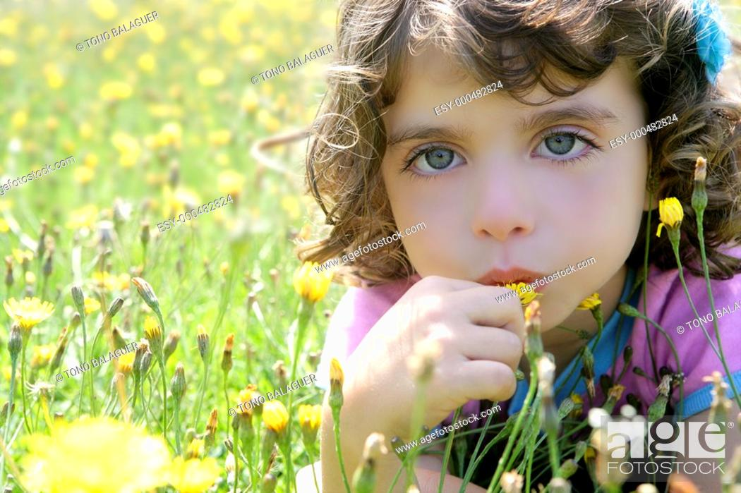 Stock Photo: Adorable little girl smell flower in the country meadow.