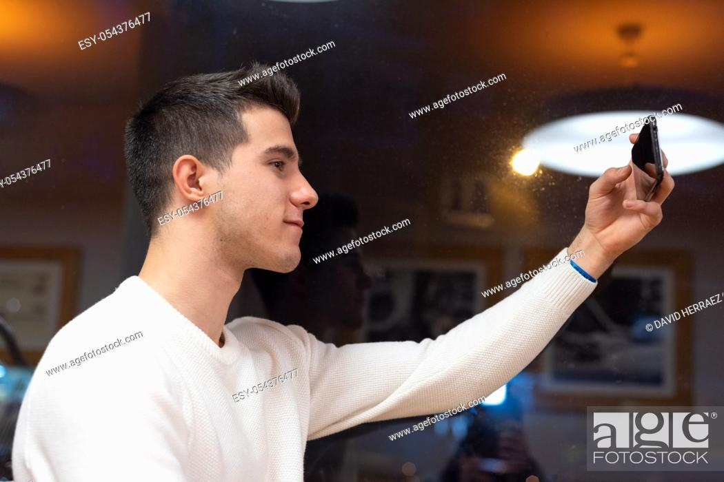 Stock Photo: Portrait of Happy young man taking selfie at the coffee shop .