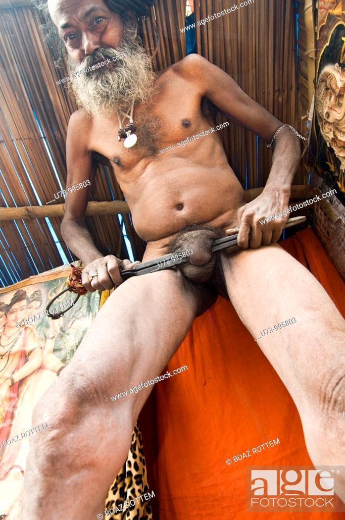 Stock Photo: A Naga sadhu performing bizarre act.
