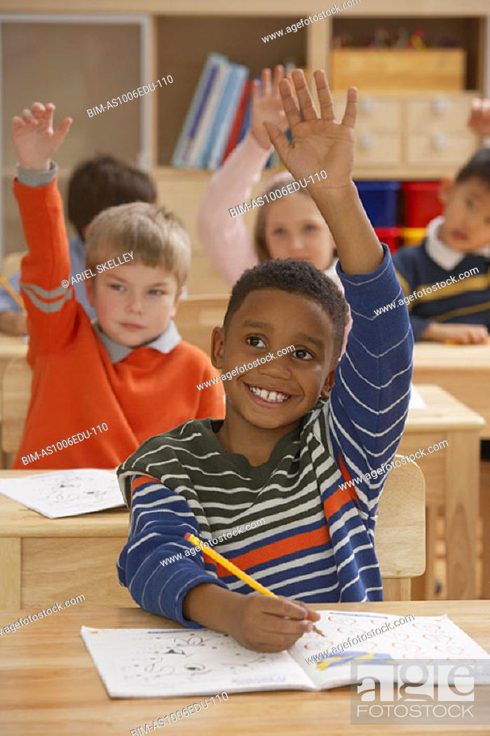 Stock Photo: Students raising hands in classroom.