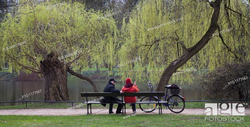 Stock Photo: People sitting on a bench at Royal Baths Park, Warsaw Poland.