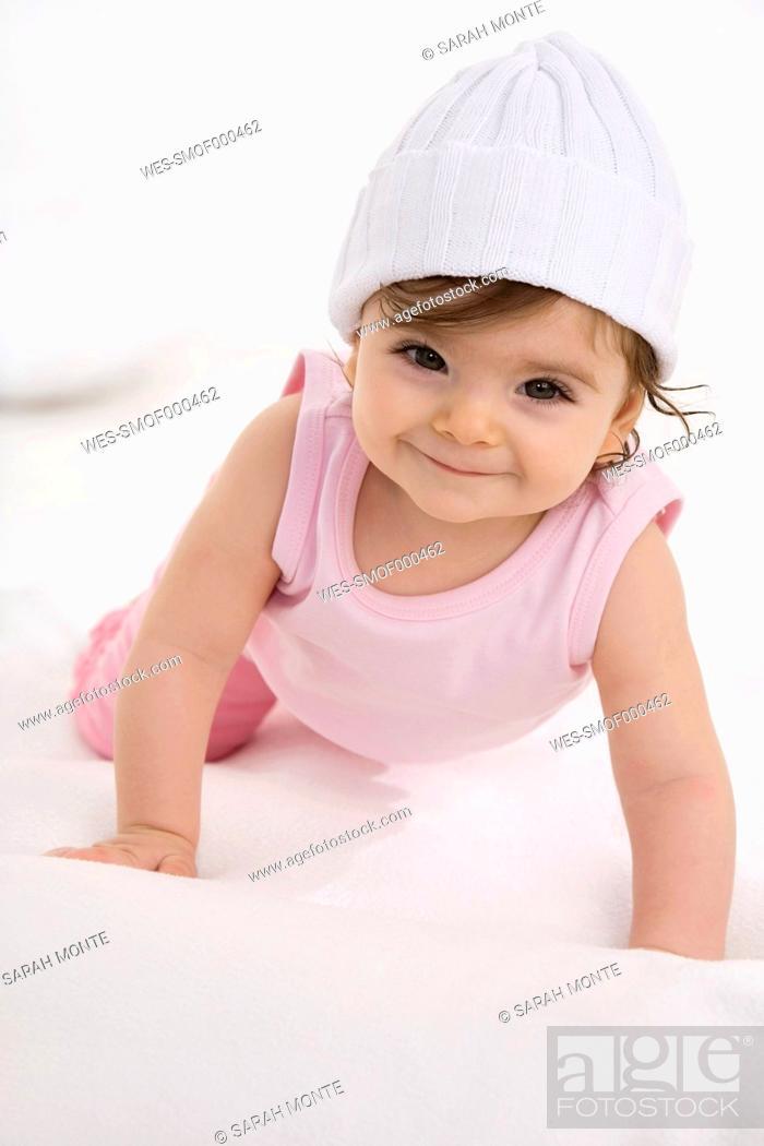Stock Photo: Baby girl crawling on baby blanket.
