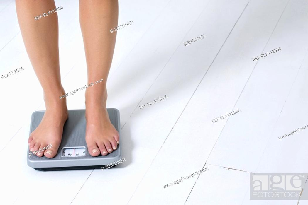 Stock Photo: Young woman weighing herself.