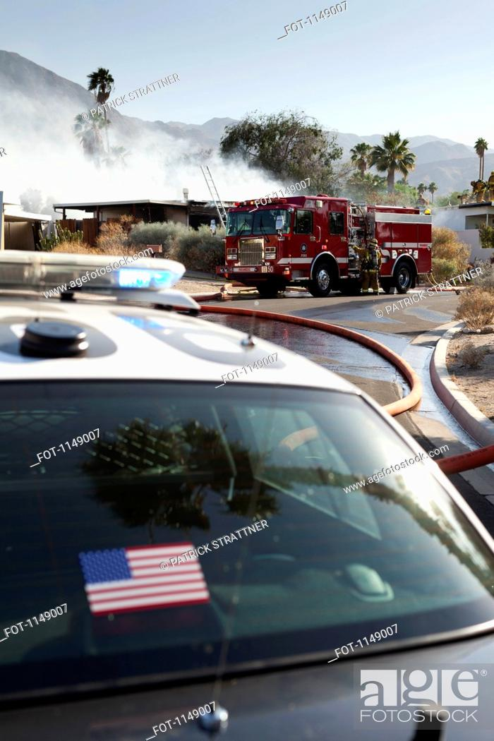 Stock Photo: A police car and a fire truck at the scene of a burning house in a suburb.