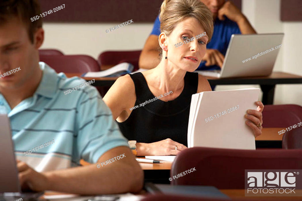 Stock Photo: Close-up of a mid adult woman sitting in a lecture hall and peeking at a young man during an exam.
